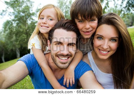 Happy Young Family Taking Selfies With Her Smartphone In The Park