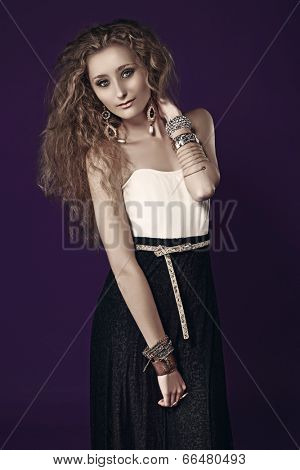 Portrait of a young beautiful woman with long blond curly hair wearing pearl earrings and gold bracelets, long black skirt against purple studio background