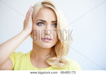 Worried beautiful young blond woman holding her head as she stares into the distance with troubled eyes  head and shoulders on grey with copyspace