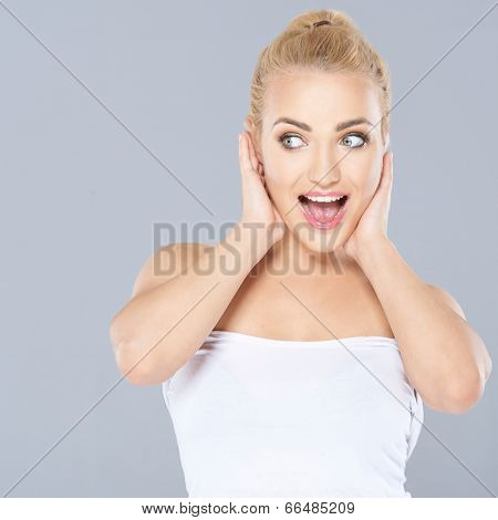 Excited beautiful young blond woman with an expression of amazement holding her hands to her cheeks and looking sideways to the left
