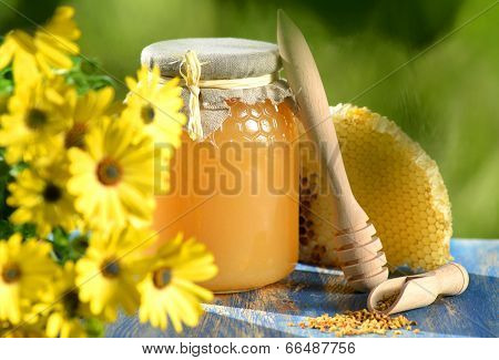 jar full of delicious honey, honeycomb and bee pollen in apiary