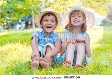 Two smiling kids sitting on green grass in a park