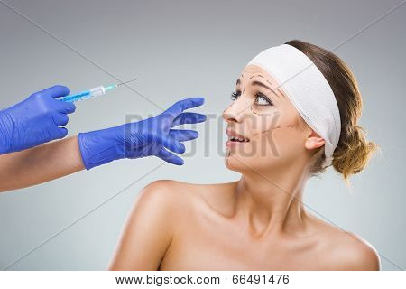 Beautiful woman with plastic surgery, the fear of the needle