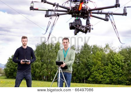Professional team of a photographer and pilot operating a UAV Photography Drone