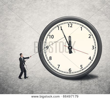 Asian businessman trying to turn back time by pulling on a rope attached to the hands of a clock.