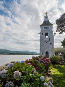 stock photo of beachfront  - Tower at the beachfront of the small Welsh village of Portmeirion along the estuary of the river Dwyryd leading into Tremadog Bay in North Wales - JPG