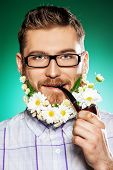 stock photo of peace-pipe  - Handsome young man in glasses and a beard of flowers smoking a pipe - JPG