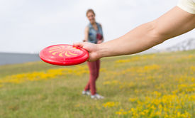 foto of frisbee  - Young couple playing frisbee on the grass in a park - JPG