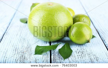 Ripe sweetie and limes on wooden background