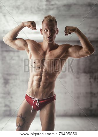 Handsome Blond Muscular Shirtless Young Man Doing Biceps Pose