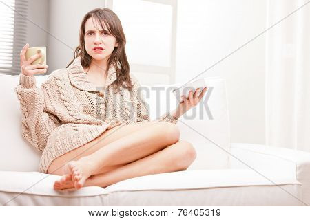 Perplexed Young Woman With Tea And Tablet