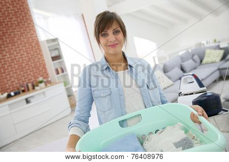 Young home service woman holding basket of folded laundry