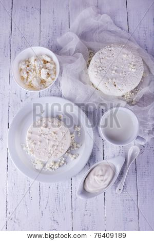 Cottage cheese on plate on gauze and cottage cheese in bowl, cup of milk and cream in saucer boat on wooden background