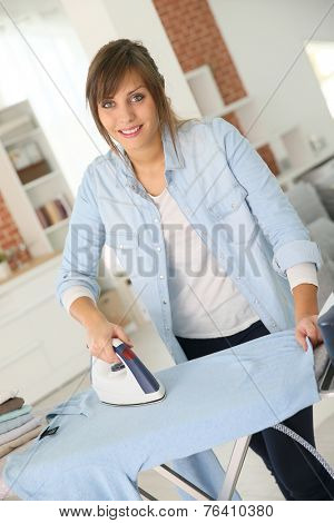 Young home service woman ironing laundry