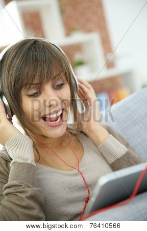 Young woman with headphones websurfing on tablet