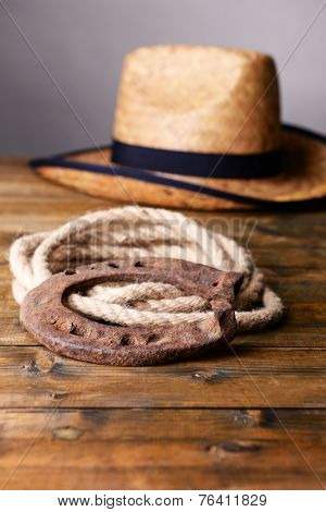 American West still life with old horseshoe, hat and cowboy lasso, on grey background