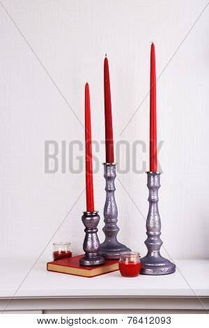 Candles in candle holders, vase and book on table on light background