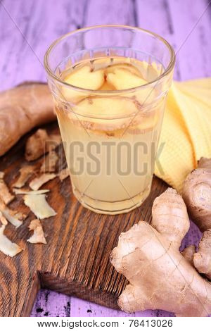 Ginger drink and ginger root and napkin on cutting board on wooden background