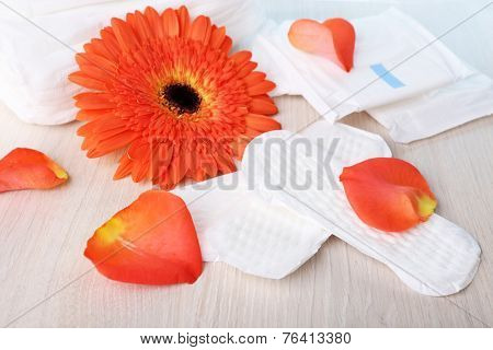 Sanitary pads, orange flower and rose petals on wooden table background
