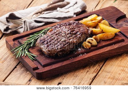 Medium Rare Grilled Beef Steak Ribeye With Roasted Potato Wedges On Cutting Board On Dark Wooden Bac
