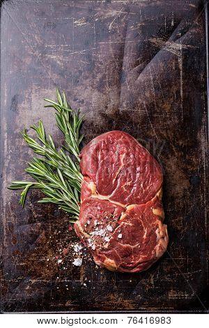 Raw Fresh Meat Ribeye Steak And Rosemary On Dark Background