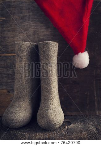 Christmas Santa Claus's Hat And Felt Boots On Wooden Background