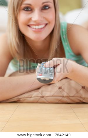 Jolly Blond Woman Watching Tv Lying On The Floor