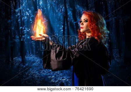 Young witch in the night forest holds fire