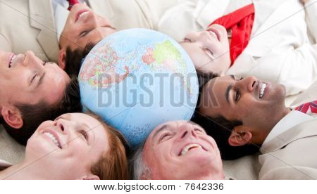 Multi-ethnic Business People Lying Around A Globe