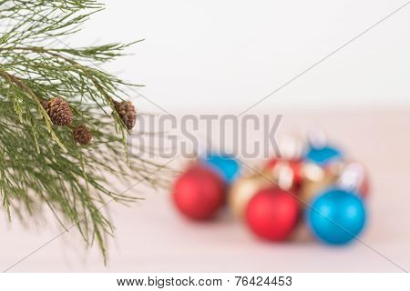 Pine Tree Branch With Red, Blue And Gold Christmas Baubles