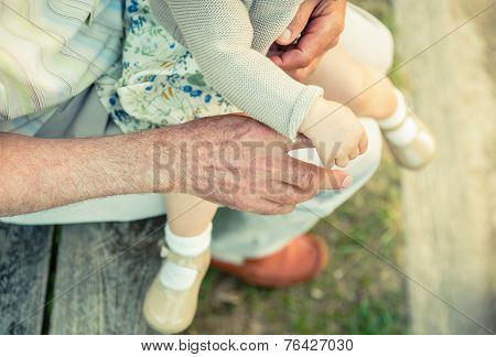 Baby girl holding finger of senior man hand