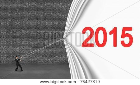 Businessman Pulling Down 2015 Curtain Covering Old Gray Brick Wall