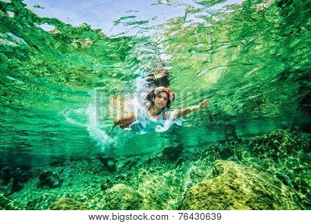 Beautiful woman in the sea, swimming underwater, wearing white dress and stylish flowers wreath, happy summer vacation concept