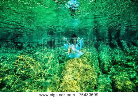 Underwater swimming, beautiful girl enjoying transparent refreshing water, summer vacation on tropical island, diving to coral garden on sea bottom