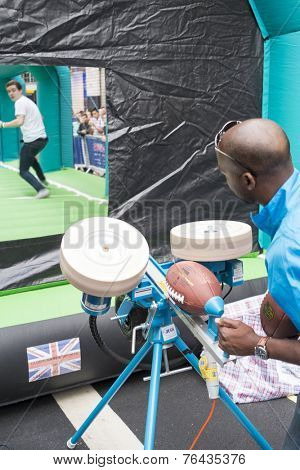 LONDON UK - SEPTEMBER 27: Man using launcher to throw American football ball to receiver in Regent St. September 27 2014 in London. The street was closed to host NFL related games and events.