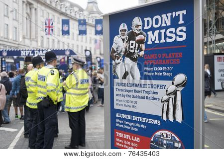 LONDON, UK - SEPTEMBER 27: NFL billboard with British policemen standing in the background. September 27, 2014 in London. Regent street was closed to traffic to host NFL related games and events.