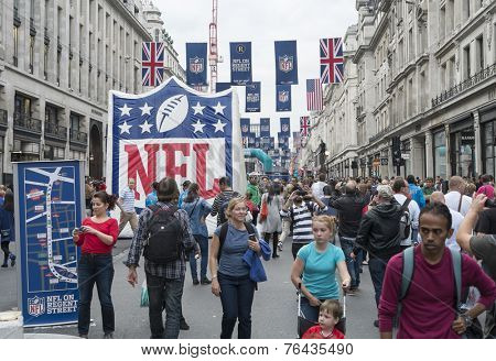 LONDON UK - SEPTEMBER 27: Crowded Regent street with NFL inflatable banners and flags hanging above. September 27 2014 in London. The street was closed to traffic to host NFL related games and events.