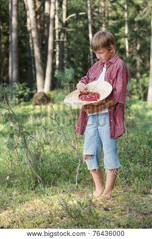 Teenage boy tasting fresh forest wildberries