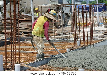 Construction Workers Using Concrete Vibrator