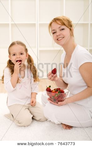 Woman And Little Girl Eating Fresh Strawberries
