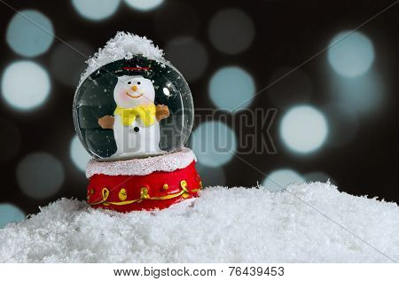 Snow globe with snowman over christmas lights background