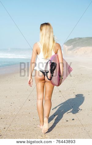 A beautiful surfer girl walking at the beach with her surfboard