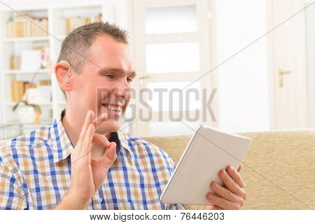 Smiling Deaf man talking using sign language on the tablets's cam
