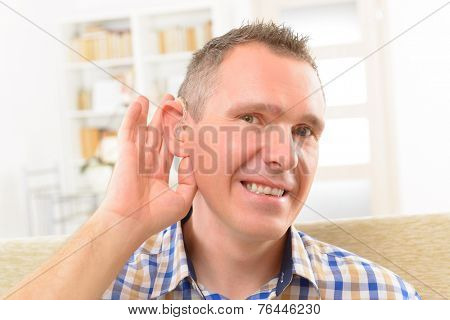 Man showing deaf aid in ear
