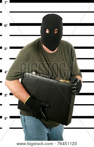 A Burglar in a Black Ski Mask, with Black Gloves is booked by the Police and his Mug Shot aka MUGSHOT taken. Bad Guys who get caught get mug shots. Holding his stolen property in the photo. Bad man