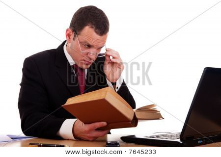 Businessman On Desk Reading And Studying, Isolated On White Background, Studio Shot.