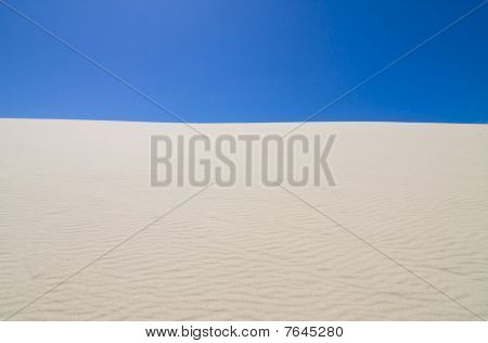 Deep blue sky against rippled sand dune