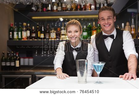 Colleagues smiling at the camera in a bar