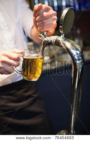 Handsome barkeeper pulling a pint of beer in a bar