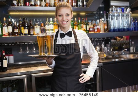 Waitress with hand on hip holding a tray of champagne in a bar